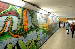 Bahnunterführung an der S-Bahn Station Nettelnburg in Hamburg Neuallermöhe, buntes Graffiti - Feuer sprühender Drachen  - auf den Kachelwänden.