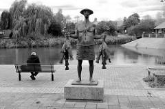 Grachtenteich am Grachtenplatz im Hamburger Stadtteil Neuallermöhe; einsamer Mann auf der Parkbank - Bronzeskulptur Fischer, Bildhauer Gerhard Brandes.
