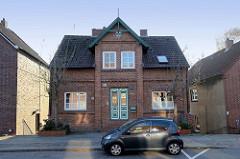 Einzelhaus im Baustil der Gründerzeit in Ziegelbauweise am  Neßdeich von Hamburg Finkenwerder. Das Wohnhaus wurde 1895 errichtet, die Holztür ist mit Schnitzwerk versehen und farblich abgesetzt.
