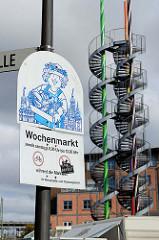 Fleetplatz im Hamburger Stadtteil Neuallermöhe, Hinweisschild auf den Wochenmarkt - dahinter die Wendeltreppen und bunten Rohre der sogenannten Zuckerstangen. Ein Kunstprojekt des Stadtteils, das als begehbares Kunstwerk hat eine Höhe von 25 m hat -