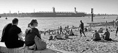 Nachmittag am Elbstrand vor Hamburg Övelgönne; die Hamburgerinnen sitzen im Sand und blicken auf die vorbeifahrenden Frachtschiffe.