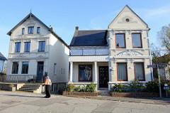 Wohnhäuser, Einzelhäuser mit glasierten weißen Ziegeln und Stuckornamentik an der Hausfassade, Straße Sandhöhe im Hamburger Stadtteil Finkenwerder.