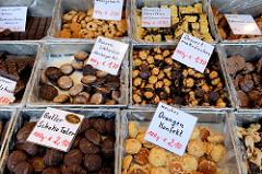 Marktstand mit Keksen  auf dem Wochenmarkt am Quarree im Hamburger Stadtteil Wandsbek; frisch gebackene Kekse wie zum Beispiel Dessert-Makrönchen, Orangen-Konfekt oder Butter Schoko Taler liegen in der Auslage.