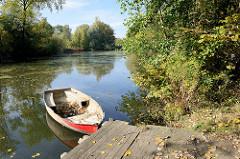 Bootsteg mit rotem Ruderboot an der Hövelpromenade der Dove Elbe im Hamburger Stadtteil Wilhelmsburg.