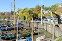 Historische Boote im Museumshafen Hamburg Övelgönne - am Ufer ein historischer Hafenkran.