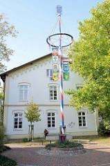 Europaplatz von Trittau, Wappen der Städte Freundschaften hängen an einem Maibaum.
