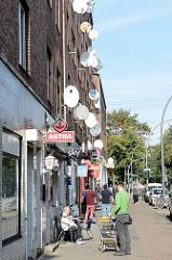 Straßenszene in Hamburg Wilhelmsburg, Georg Wilhelm Straße; Kioske mit Stühlen auf dem Gehweg, an der Hauswand Satellitenschüsseln.