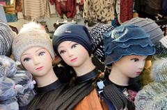 Marktstand für Bekleidung auf dem Wochenmarkt in Hamburg Finkenwerder, Finksweg; Puppenköpfe mit aufgemalten Augen und roten Lippen tragen Wollmützen.
