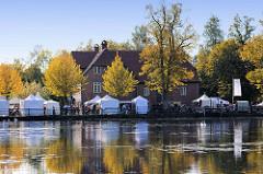 Blick über den Trittauer Mühlenteich zu den historischen Gebäuden der Wassermühle; Zelte vom dort stattfindenden Handwerkermarkt.