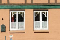 Fenster mit aufgesetzter Verleistung / Zierleisten und Gardinen mit Stickereien an einem Wohnhaus in der Mühlenstraße von Boizenburg/Elbe