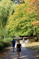 Herbst in der Hansestadt Hamburg, Besucherinnen der Grünanlage am Weiher in Eimsbüttel sitzen in der Sonne auf Parkbänken, joggen,  fahren Fahrrad oder gehen unter den Herbstbäumen spazieren.
