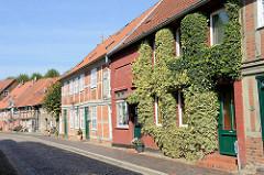 Denkmalgeschützte Wohnhäuser in der Großen Wallstraße von Boizenburg/Elbe; die Fassade eines der Gebäude ist dicht mit Efeu bewachsen. Die Straße ist mit Kopfstein- Pflaster gepflastert.
