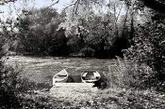 Uferidyll an der Wilhelmsburger Dove Elbe  in Hamburg Wilhelmsburg, schwarz-weiß Fotografie - zwei Ruderboote liegen am Holzsteg.