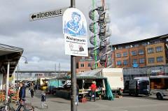 Fleetplatz im Hamburger Stadtteil Neuallermöhe, Hinweisschild auf den Wochenmarkt - dahinter die Wendeltreppen und bunten Rohre der sogenannten Zuckerstangen. Ein Kunstprojekt des Stadtteils, das als begehbares Kunstwerk hat eine Höhe von 25 m hat