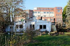 Leerstehendes Wohnhaus in schlichter Bauweise am   Neßdeich von Hamburg Finkenwerder; dahinter  die moderne Verwaltungsarchitektur des Flugzeughersteller Airbus.
