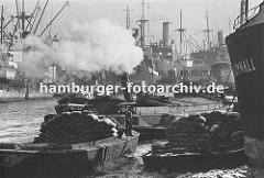 Fotodokumentation - Geschichte der Arbeit im Hamburger Hafen. Geschäftiges Treiben im Hamburger Hafen ca. 1930; Frachter liegen an den Duckdalben in der Mitte des Segelschiffhafens. Ein Schlepper zieht unter Dampf eine Schute im Hafenbecken.