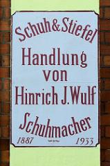 Handgemaltes  Fassadenschild Schuh & Stiefel, Handlung von Hinrich J. Wulff Schumacher an der Hausfassade eines denkmalgeschützten Gebäudes am Auedeich in Hamburg Finkenwerder.