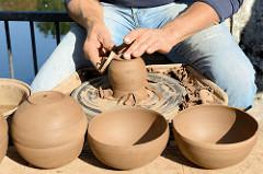 Trittauer Kunsthandwerkermarkt zum Erntedankfest an der historischen Wassermühle. Ein Töpfer dreht seine Keramik von Hand auf der Töpferscheibe.