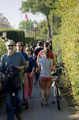 Schmaler Fußweg Övelgönne am Elbufer in Hamburg Othmarschen;  Fahrradfahrerinnen sind angehalten ihr Fahrrad zu schieben.
