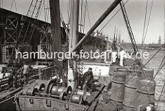 Historische Fotografien aus dem Hamburger Fotoarchiv. Blick über das Deck eines Frachtschiffs im Segelschiffhafen - ein Arbeiter steht an der elektrischen Winde, die den Ladebaum des Schiffs betreibt.