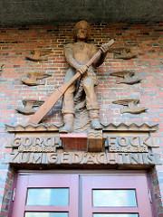 Richard Kuöhl gefertigte Keramikskulptur eines Fischers über dem Eingang der Veranstaltungshalle in Hamburg Finkenwerder. Die Gorch Fock Halle wurde 1929 fertig gestellt, Architekt Fritz Schumacher.