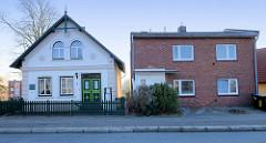 Historische Architektur neben  schlichten Nachkriegsgebäude am   Neßdeich von Hamburg Finkenwerder. Links das unter Denkmalschutz stehende Fischerhaus, erbaut 1880 - Elternhaus des Schriftstellers Gorch Fock.
