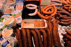 Marktstand mit Wurstspezialitäten auf dem Hamburger Wochenmarkt in Farmsen-Berne, Berner Heerweg. Würste, die nach traditionellen schlesischen Rezepten in der Nähe von Hamburg hergestellt werden.