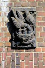 Keramikbild / Terrakottafliese in der Hausfassade eines Wohngebäudes in Trittau. Nest mit jungen Vögeln, die gefüttert werden.