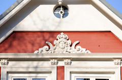 Hausgiebel mit Stuckdekor über dem Fenstersims in der Emder Straße von Hamburg Finkenwerder - Fassade eines denkmalgeschützten Wohnhauses.