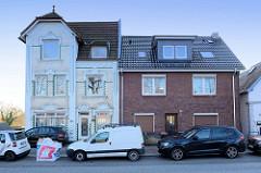 Wohnhäuser / Einzelhäuser  in der Straße Finkenwerder Norderdeich im Hamburger Stadtteil  Finkenwerder. Jugendstilvilla mit weiß glasieren Ziegeln grünen Bändern und floralen Stuckdekor, daneben ein schlichter Wohnblock aus der Nachkriegszeit.