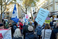 """Aktionstag der überparteilichen Sammlungsbewegung Aufstehen - Abschlusskundgebung der Demonstration mit dem Motto""""Würde statt Waffen"""" auf dem Spitzenplatz von Hamburg Altona; Protestschilder."""