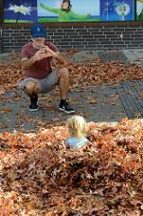 Herbst in der Marktpassage von Hamburg Neugraben, ein Kind spielt im Herbstlaub.