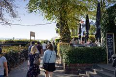 Fußweg Övelgönne am Elbufer von Hamburg Othmarschen / Ottensen; Restaurants und Cafés haben Tische im Garten unter Bäumen aufgestellt.