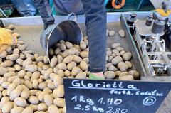 Kartoffelstand auf dem Hamburger Wochenmarkt Farmsen-Berne; ein Markthändler füllt Kartoffeln in eine Waagschale.
