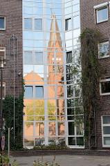 Spiegelung der Sankt Bonifatius Kirche  in der Glasfassade eines Gebäudes; Bilder aus Hamburg Wilhelmsburg - Architektur der Stadt.