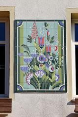 Farbenfrohe Fliesen mit bunten Blumen   / Blüten  auf Boizenburger Keramik an der Hauswand eines Blumengeschäftes in der Königstraße von Boizenburg/Elbe.