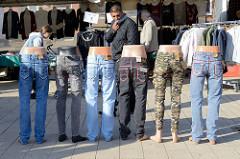 Wochenmarkt in Hamburg Wilhelmsburg / Stübenplatz, Stand mit Kleidung - untere Teile von Kleiderpuppen tragen verschiedene Jeans.