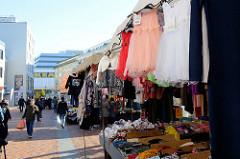 Marktstand mit Kleidung auf dem Wochenmarkt in der Großen Bergstraße, Stadtteil Hamburg Altona / Altstadt; Kleider und Blusen hängen zur Ansicht am Dach des Standes.