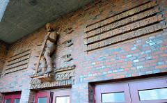 Reliefinschrift - Zitat  vom Heimat-Schriftsteller Gorch Fock  - von Richard Kuöhl gefertigte Keramikskulptur eines Fischers über dem Eingang der Veranstaltungshalle in Hamburg Finkenwerder. Die Gorch Fock Halle wurde 1929 fertig gestellt, Architek