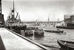Historische Hafenmotive aus dem Hamburger Fotoarchiv. Am Amerikakai des Segelschiffhafens liegt der schwedische Frachter KNUT aus Trelleborg - die Ladung der Schuten ist teilweise mit Persenning gegen Witterungseinflüsse abgedeckt. Ein Jollen