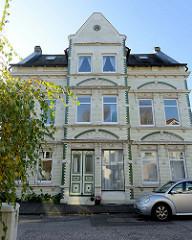 Jugendstil Wohnhaus mit weiß glasierten Kacheln und grünen Bändern im Auedeich von Hamburg Finkenwerder; in dem unter Denkmalschutz stehenden Gebäude war früher eine Bäckerei / Konditorei untergebracht.