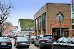 Einkaufstraße /  Wedeler Landstraße im Hamburger Stadtteil Rissen; moderne Architektur und historisches Reetdach-Haus  stehen in der schmalen Geschäftsstraße dicht nebeneinander.