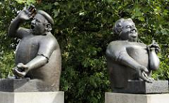 Bronzeskulptur Marktschreier am Lohbrügger Markt  im Hamburger Stadtteil Lohbrügge, Bildhauer Dr. János Enyedi 1989. Eine rundliche Marktfrau hält in der einen Hand das Wechselgeld und in der anderen eine Tüte mit Früchten. Dahinter steht der Marktsc