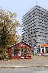 Holzhütte als Weltladen in der Rissener Dorfstraße im Hamburger Stadtteil Rissen, dahinter ein Hochhaus, das zur Renovierung eingerüstet ist.