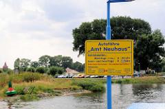 Blick über die Elbe zum Fähranleger Bleckede - Schild  der Autofähre Amt Neuhaus mit Betriebszeiten.