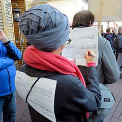 """Aktionstag der überparteilichen Sammlungsbewegung Aufstehen - Abschlusskundgebung der Demonstration mit dem Motto""""Würde statt Waffen"""" auf dem Spitzenplatz von Hamburg Altona.  Auf vorgedruckten Schecks konnten Passanten eintragen, was sie mit den 43"""