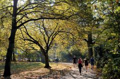 Herbst in der Hansestadt Hamburg, Besucherinnen der Grünanlage am Weiher in Eimsbüttel joggen  oder gehen unter den Herbstbäumen spazieren.