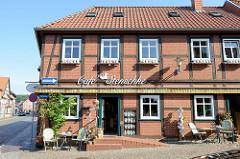Café in der Straße Fiefhusen in Boizenburg/Elbe;  Tische auf dem Kopfsteinpflaster -eine Sammlung von Kaffeekannen in der Außenvitrine.