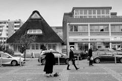 Wohn- und Geschäftshäuser in der Wedeler Landstraße in Hamburg Rissen; Reetdach Haus und moderne Architektur der 1970er Jahre  stehen direkt nebeneinander.