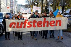 """Aktionstag der überparteilichen Sammlungsbewegung Aufstehen - r Demonstration mit dem Motto Würde statt Waffen in der Max-Brauer-Allee in Hamburg Altona. Transpart mit roter Aufschrift """"aufstehen""""."""
